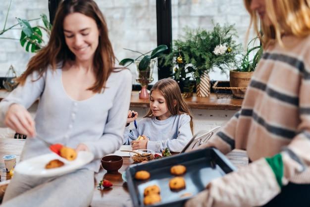 A menina aprende as lições na cozinha enquanto a mãe e a amiga fazem o jantar.