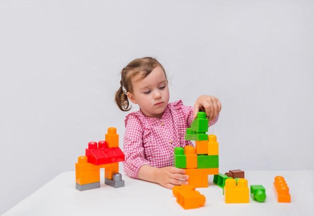 A menina aprende construir de um construtor em um fundo branco.