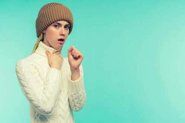 A menina apresenta sintomas de coronavírus. gripes e resfriados. retrato de mulher jovem e bonita com tosse e dor de garganta, sensação de enjôo dentro de casa. close de uma mulher doente e insalubre tossindo