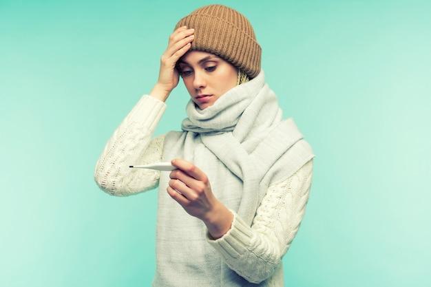 A menina apresenta sintomas de coronavírus. jovem mulher com termômetro de tomada de combustão contra o espaço azul. bela dama está doente com febre alta e dor de cabeça. resfriado, conceito de gripe.