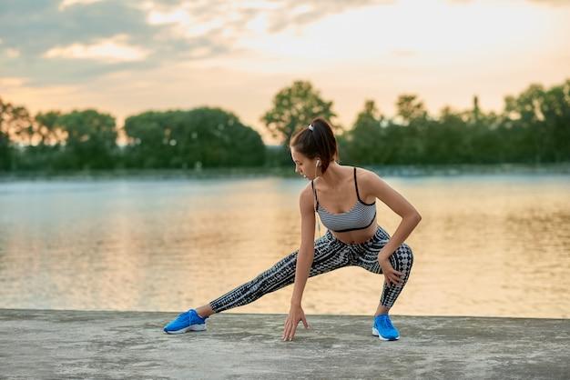A menina apta que faz a aptidão exercita fora na noite. vestindo sportwear moderno elegante.