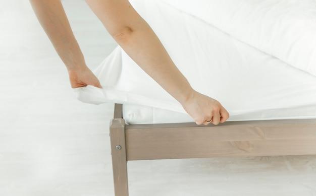 A menina arruma a cama com um cobertor