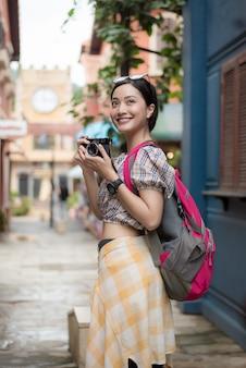 A menina asiática aprecia felizmente tomar a foto em urbano ao viajar.