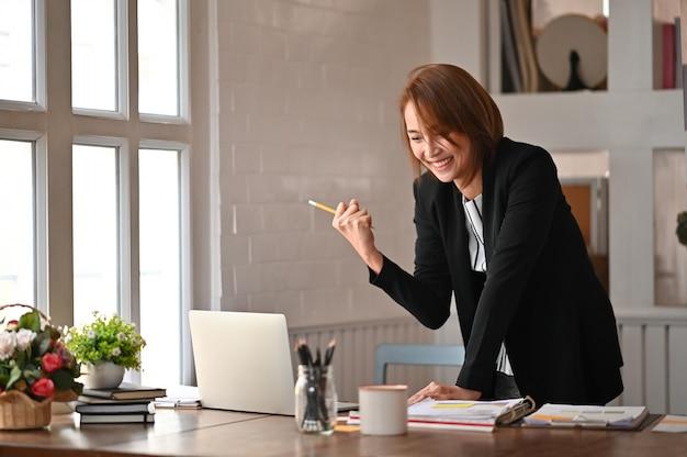 A menina asiática bonita comemora bem sucedido com braços que comemora acima a vitória no local de trabalho do escritório.