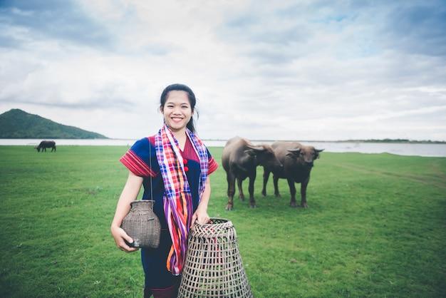 A menina asiática bonita que guarda a armadilha e a cesta de peixes, prepara-se para apanhar peixes que andam no campo perto do lago na zona rural de tailândia