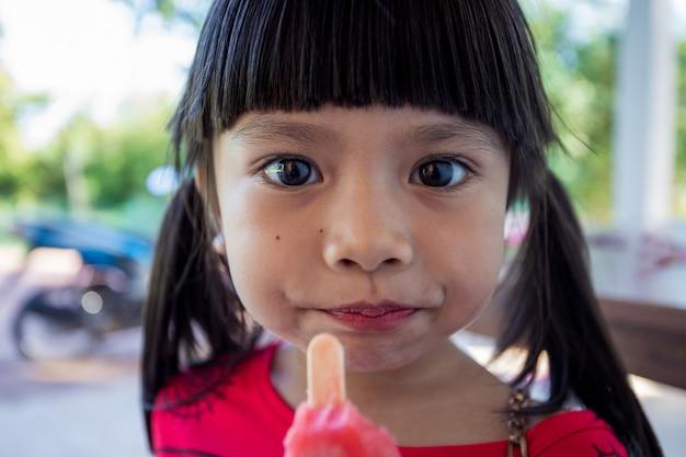 A menina asiática bonitinha está felizmente comendo sorvete.