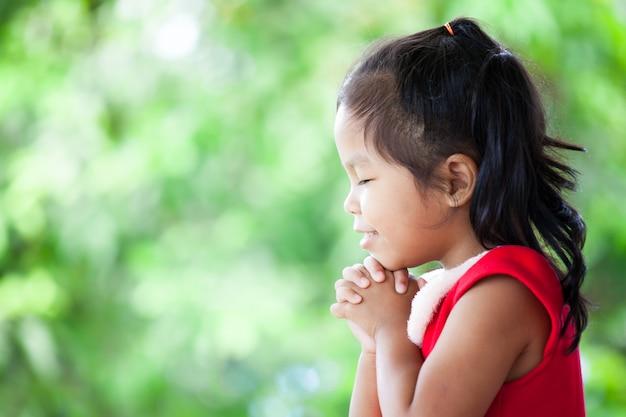 A menina asiática bonito no vestido do natal fechou seus olhos e dobrou sua mão na oração