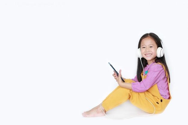 A menina asiática consideravelmente pequena que usa o smartphone a aprecia a música de escuta com os fones de ouvido isolados com copyspace.