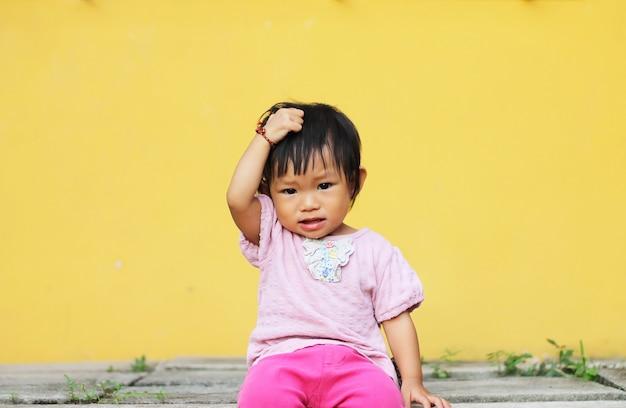 A menina asiática da criança do bebê pôs sua mão sobre sua cabeça.