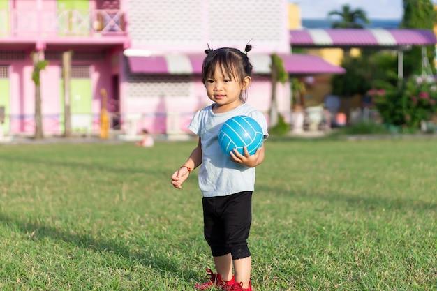 A menina asiática da criança do bebê que joga e que guarda uma bola brinca no campo de jogos do campo.