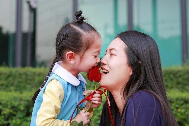 A menina asiática da criança e sua mãe com beijo aumentaram no jardim.