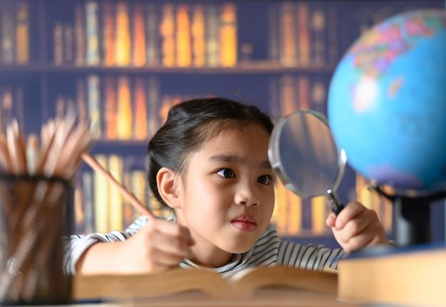 A menina asiática da criança industriosa está sentando-se em uma mesa dentro. kid está aprendendo em casa