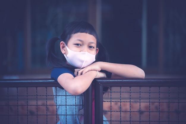A menina asiática da criança pequena do retrato que veste a máscara protetora fica em casa durante o fechamento covid-19 para baixo.