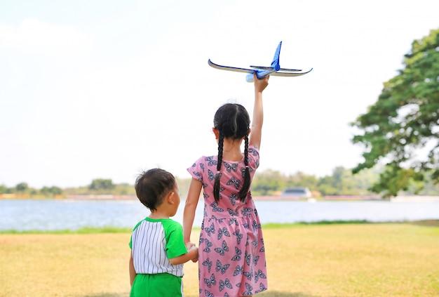 A menina asiática da criança pequena guarda o bebê das mãos e levanta um avião azul do brinquedo que voa no ar no jardim da natureza. irmã e seu irmão em pé perto do lago no parque. visão traseira.