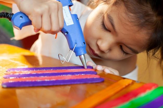 A menina asiática da criança que cola o gelado colorido cola pela pistola de cola elétrica do derretimento quente. as crianças se divertem para fazer casa em um projeto de artesanato.