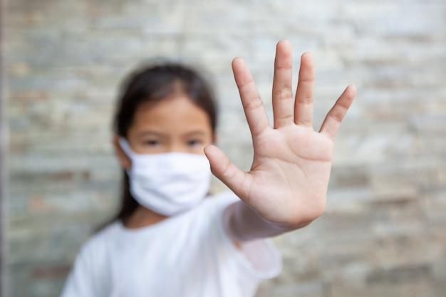 A menina asiática da criança que veste a máscara da proteção e mostra para o gesto com a mão para o surto do vírus da parada corona ela fica em quarentena em casa contra o coronavírus covid-19 e a poluição do ar pm2.5.