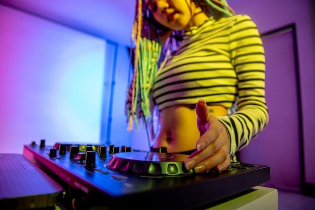 A menina asiática dj está jogando uma plataforma giratória na festa da noite é colorida.