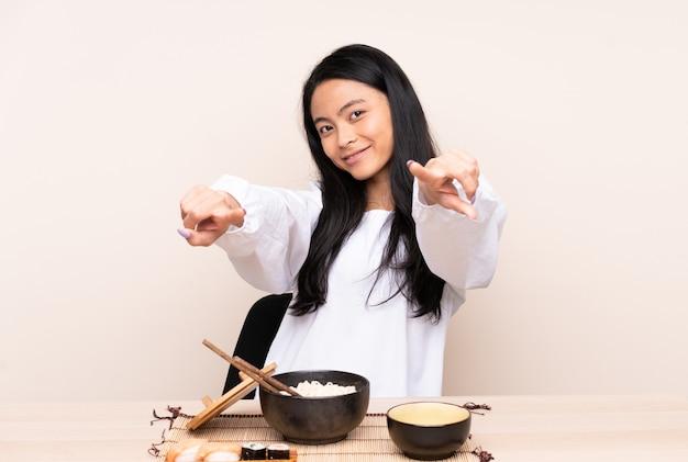 A menina asiática do adolescente que come a comida asiática isolada na parede bege aponta o dedo em você ao sorrir