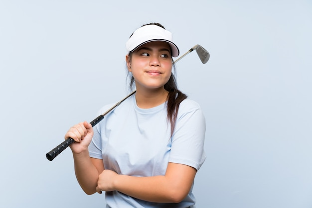 A menina asiática do jogador de golfe novo sobre a parede azul isolada que faz dúvidas gesticula ao levantar os ombros