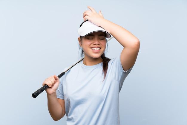 A menina asiática do jogador de golfe novo sobre o fundo azul isolado realizou algo e pretendendo a solução