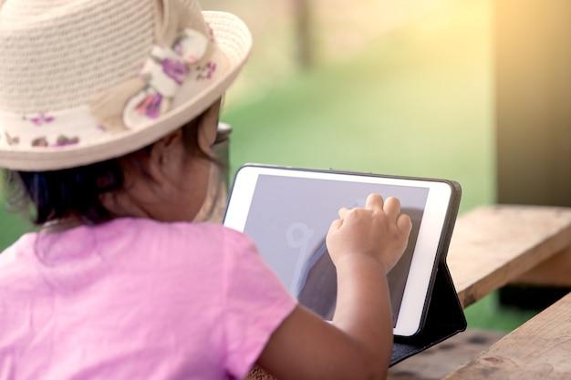 A menina asiática está jogando o tablet ipad no tom de cor vintage