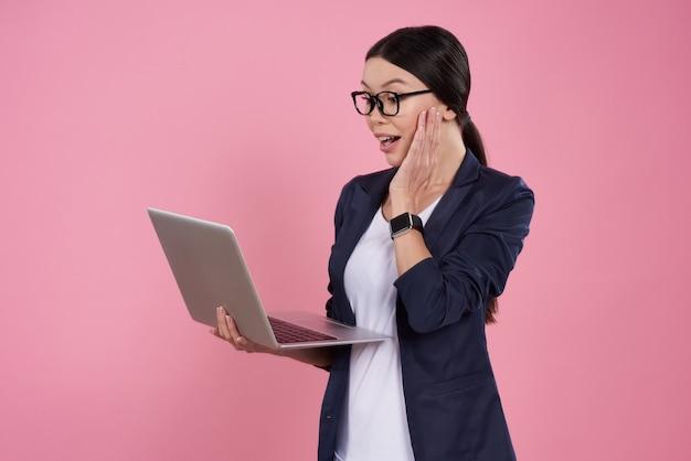 A menina asiática está levantando com o portátil no fundo cor-de-rosa.