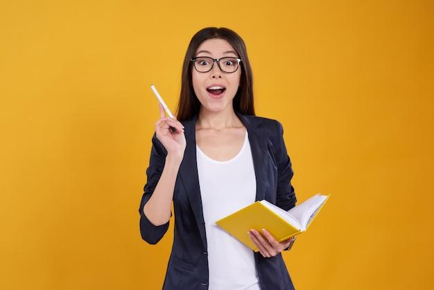 A menina asiática está levantando tomando notas isolado.