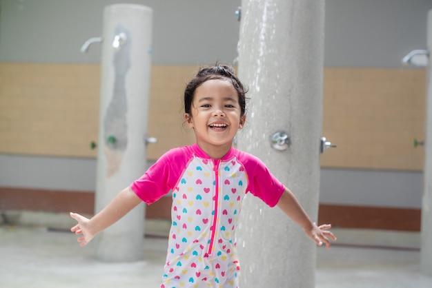 A menina asiática feliz que toma gotas da água do chuveiro cai no roupa de banho que toma o chuveiro no dia ensolarado.