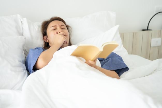 A menina asiática leu livros ao dormir.