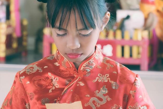 A menina asiática no vestido chinês lê no papel para prever o futuro.
