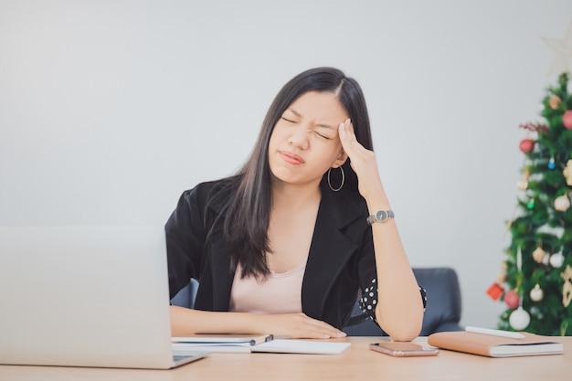 A menina asiática nova bonita que sente a dor de cabeça e o esforço no espaço de escritórios com portátil e decora o fundo da árvore de natal