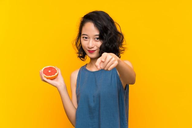 A menina asiática nova que prende uma toranja sobre a parede alaranjada isolada aponta o dedo em você com uma expressão segura