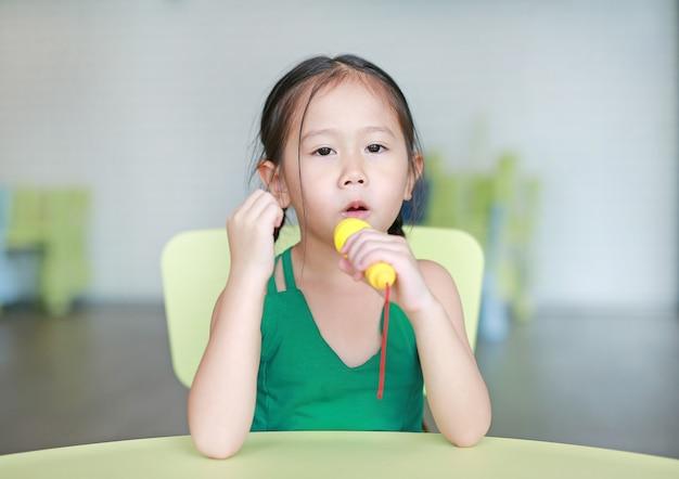 A menina asiática pequena adorável da criança canta uma música pelo microfone plástico na sala da criança.