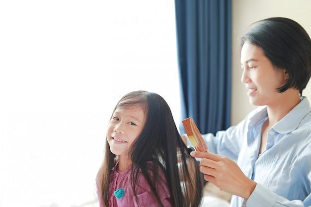 A menina asiática pequena bonita da criança com cabelo e a mamã longos vestiu-se acima para o cabelo liso na manhã na sala.