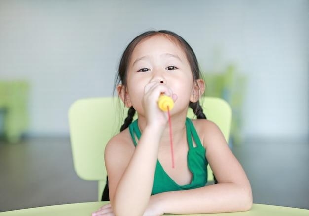 A menina asiática pequena bonito da criança canta uma música pelo microfone plástico na sala da criança.