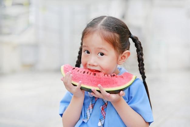 A menina asiática pequena bonito da criança na farda da escola aprecia comer a melancia cortada fresca.