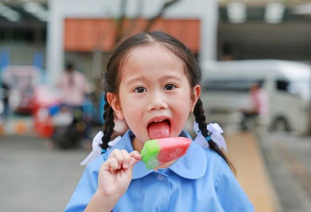 A menina asiática pequena bonito da criança na farda da escola aprecia comer o gelado no parque.