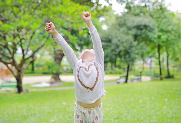 A menina asiática pequena da criança arma acima suas mãos e vista acima no jardim do verão.