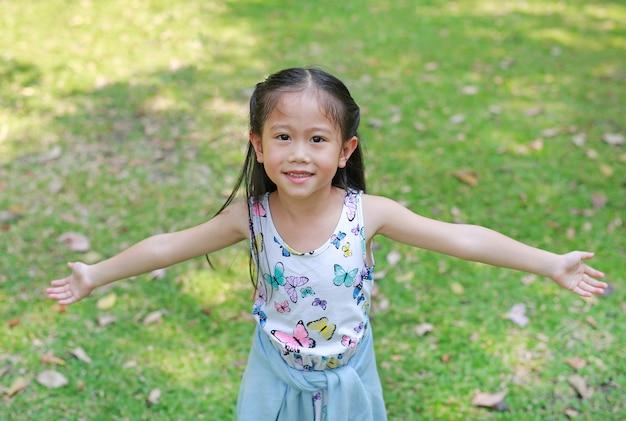 A menina asiática pequena de sorriso da criança abriu suas mãos no jardim do verão.