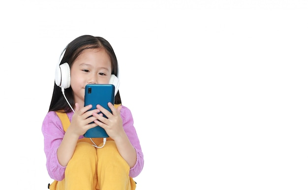 A menina asiática pequena do retrato aprecia escutar a música pelos auscultadores isolados com copyspace.