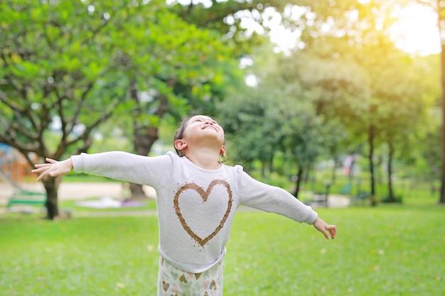 A menina asiática pequena feliz da criança abriu suas mãos e olhando acima no jardim fresco do verão.