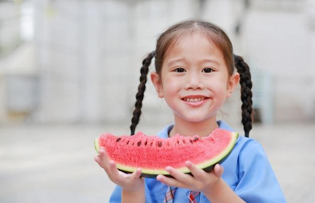 A menina asiática pequena feliz da criança na farda da escola aprecia comer a melancia fora.