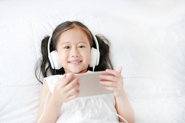 A menina asiática pequena feliz que usa fones de ouvido escuta música pelo smartphone que sorri e que olha a câmera ao encontrar-se na cama em casa.