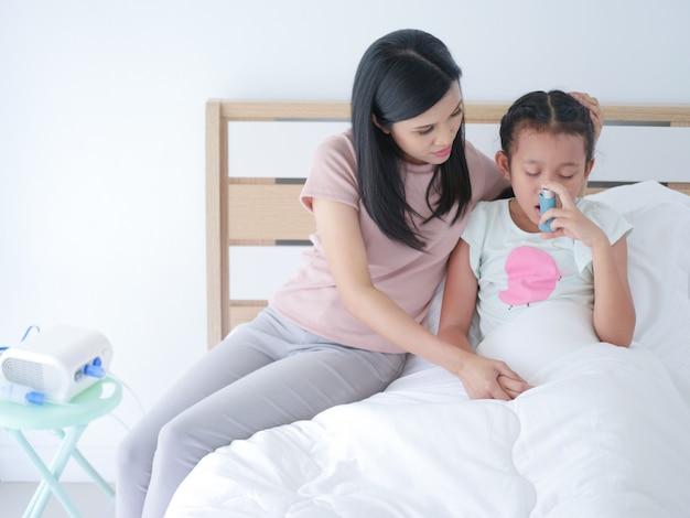 A menina asiática pequena que coloca na cama na sala de hospital e em sua mamã era ciao ao lado.
