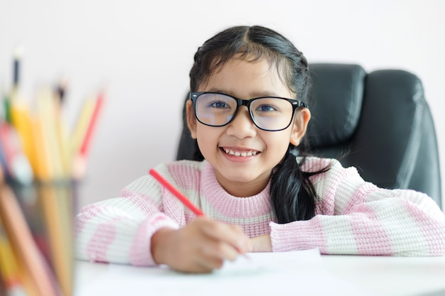 A menina asiática pequena que faz a lição de casa e sorri com felicidade para o conceito da educação seleciona a profundidade de foco rasa do campo