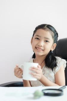 A menina asiática pequena que guarda a caneca branca e sorri com felicidade seleciona a profundidade de foco rasa do campo