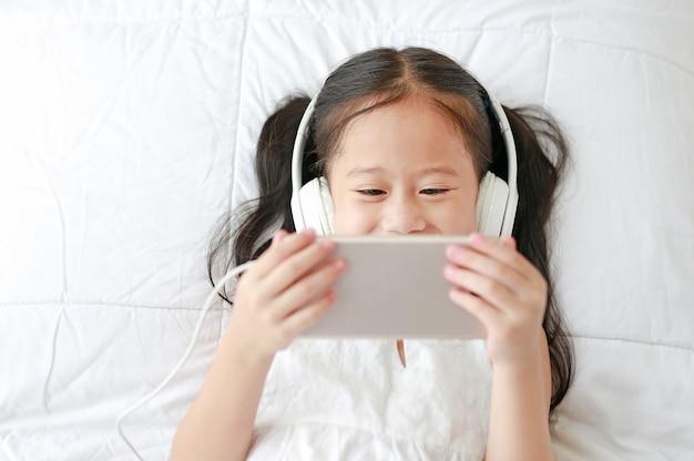 A menina asiática que usa fones de ouvido escuta música pelo smartphone que sorri ao encontrar-se na cama em casa.