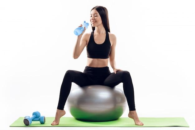 A menina asiática senta-se na esfera do gym e bebe-se a água.