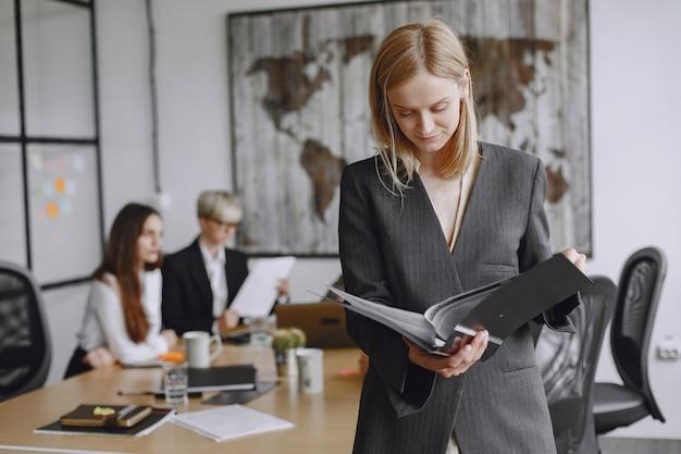 A menina assina os documentos. senhora sentada na mesa. gerente trabalhando no escritório.