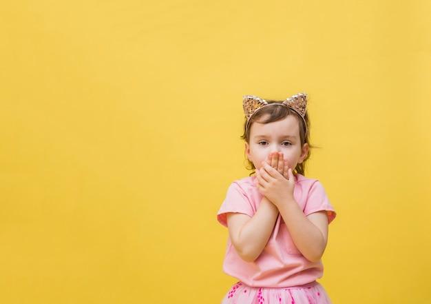 A menina assustada cobre a boca com as mãos em um espaço amarelo. uma garotinha com uma faixa de orelha de gato fica surpresa. linda garota em uma camiseta rosa com um bolso.